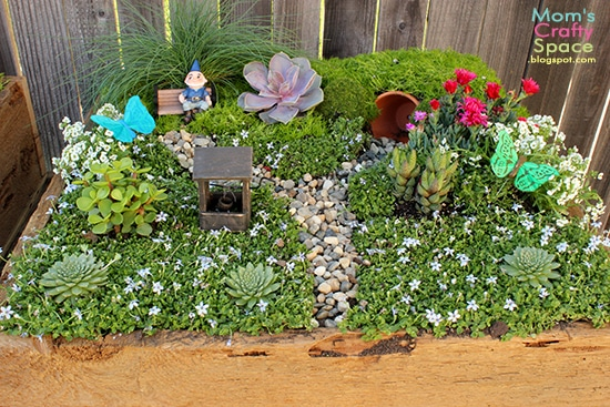 A close up of a fairy garden with plants, rocks, and miniatures