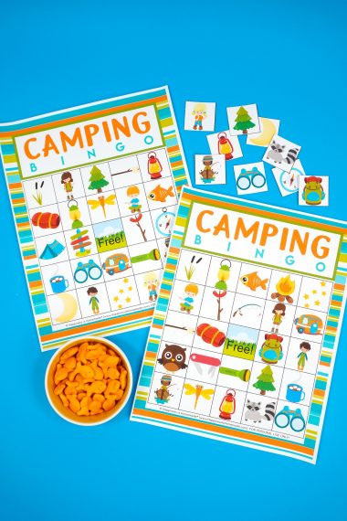Two Camping Bingo Printable game cards on a blue background with scattered calling cards and bowl of Goldfish crackers for game markers