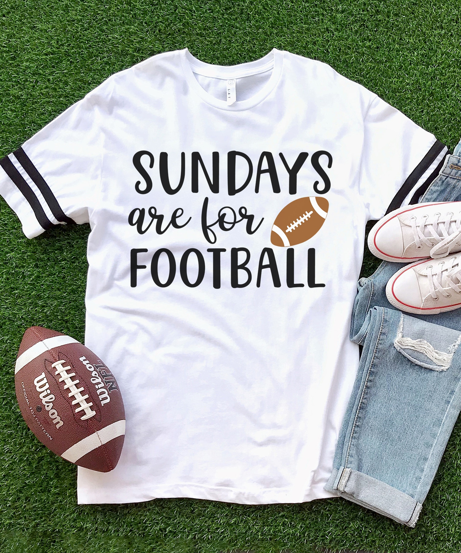 """White shirt with """"Sundays are for Football"""" graphic on a grass turf background with jeans, shoes, and a football"""