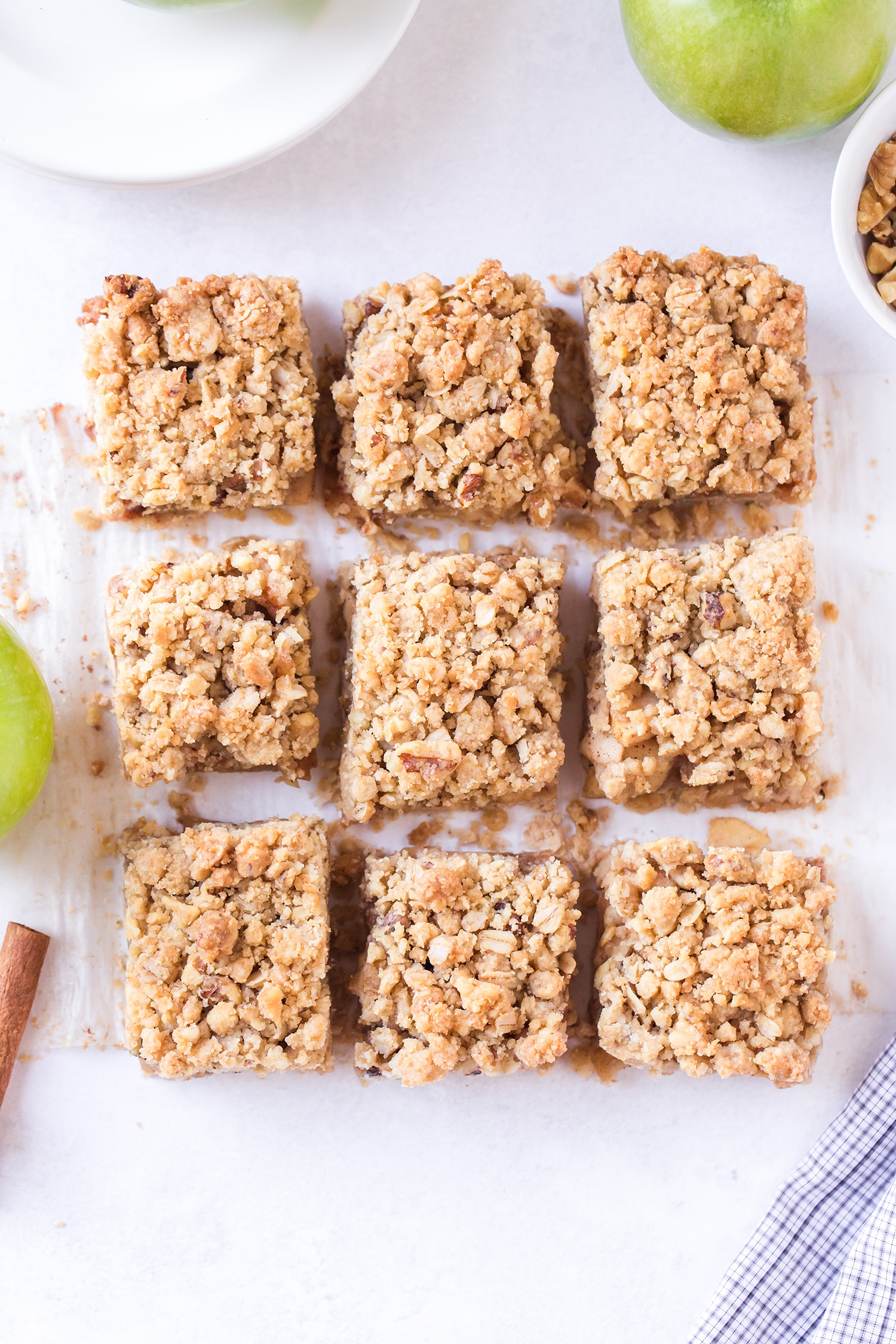 Sliced apple pie bars on white marble background surrounded by green apples and cinnamon sticks