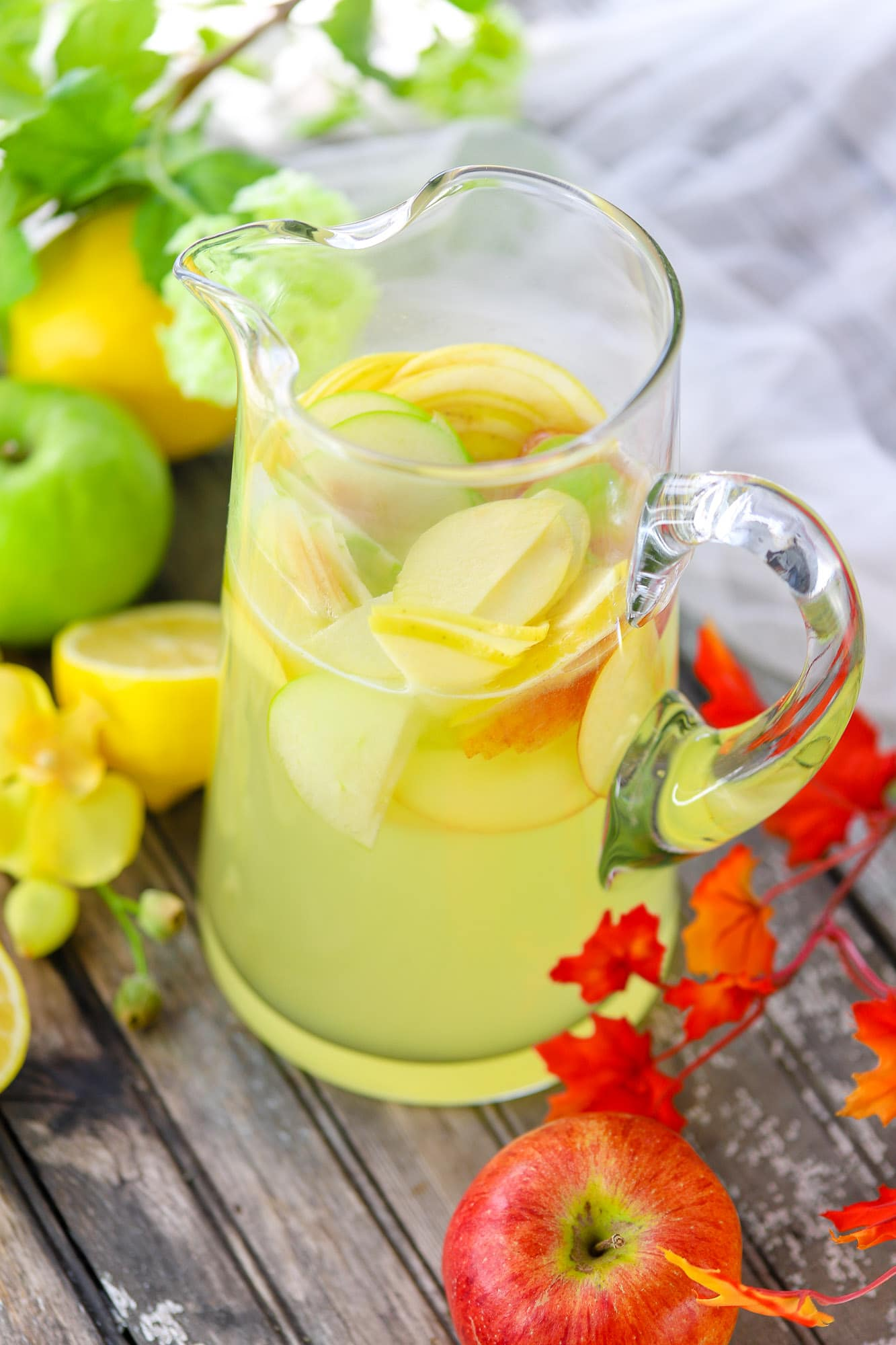 clear glass pitcher full of lemonade and apple slices surrounded by apples and lemons