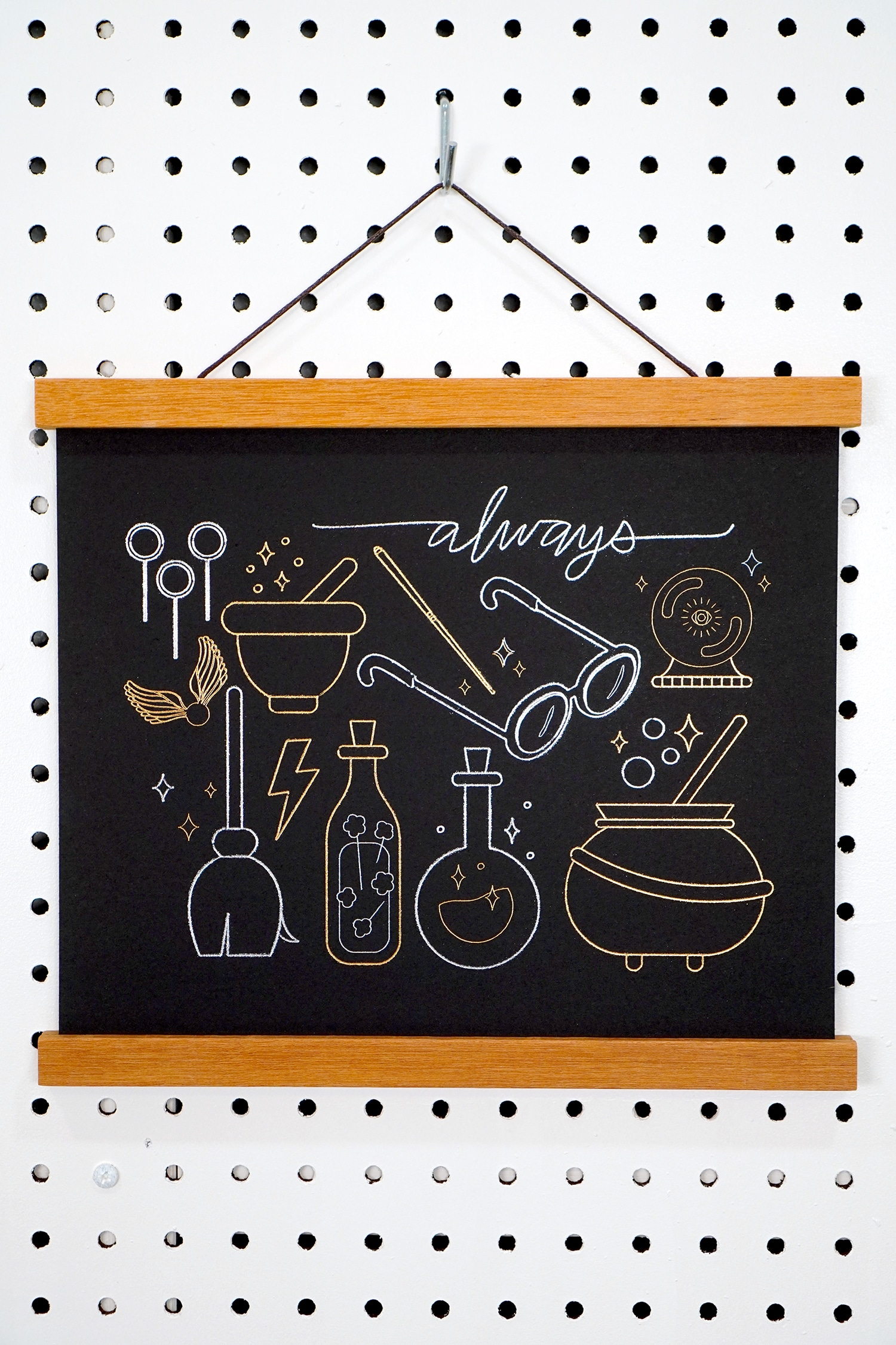 Gold and Silver Foil Harry Potter Artwork hanging on pegboard