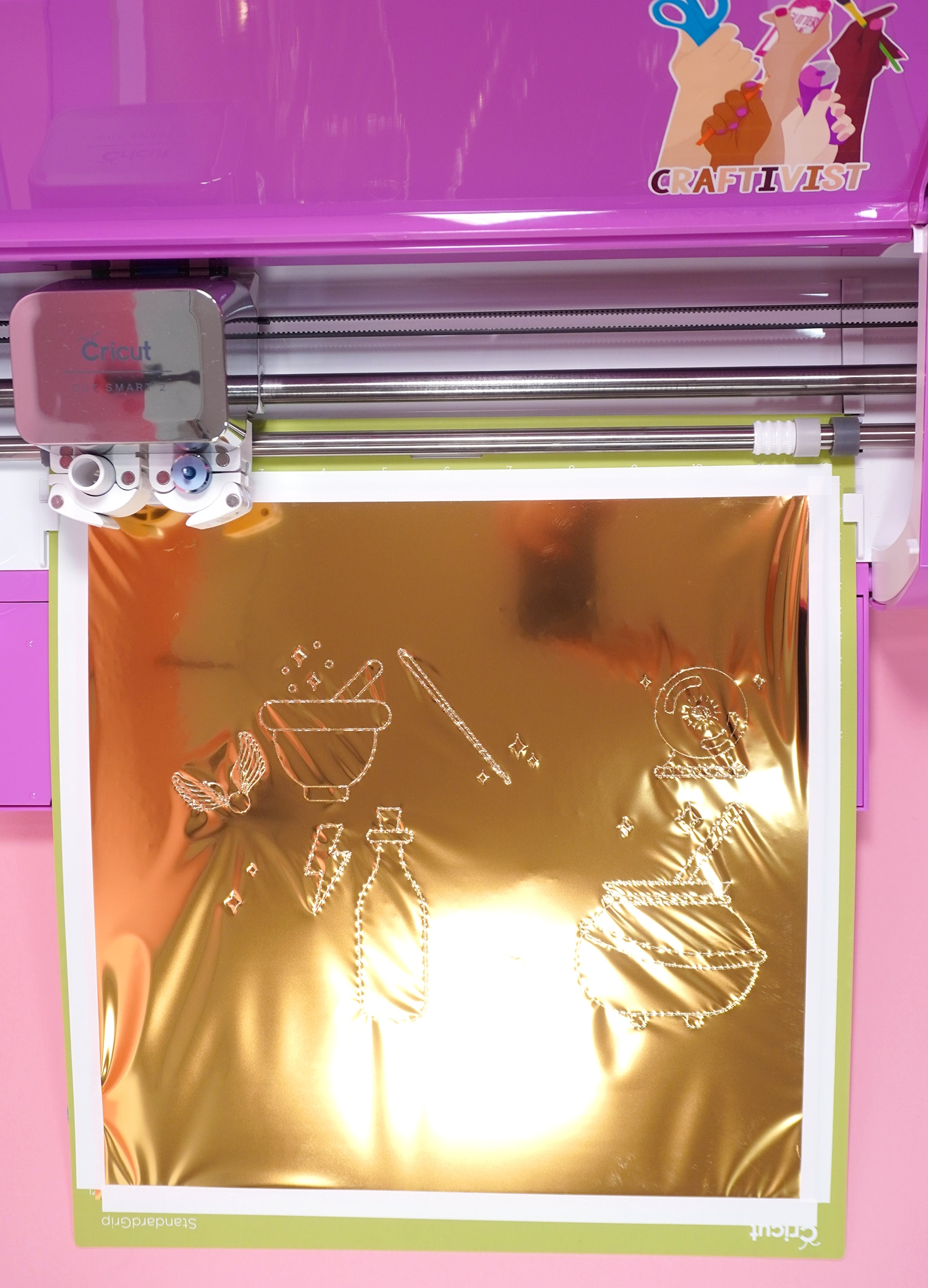 Gold foil with Harry Potter inspired designs on mat in pink Cricut Explore Air 2 machine