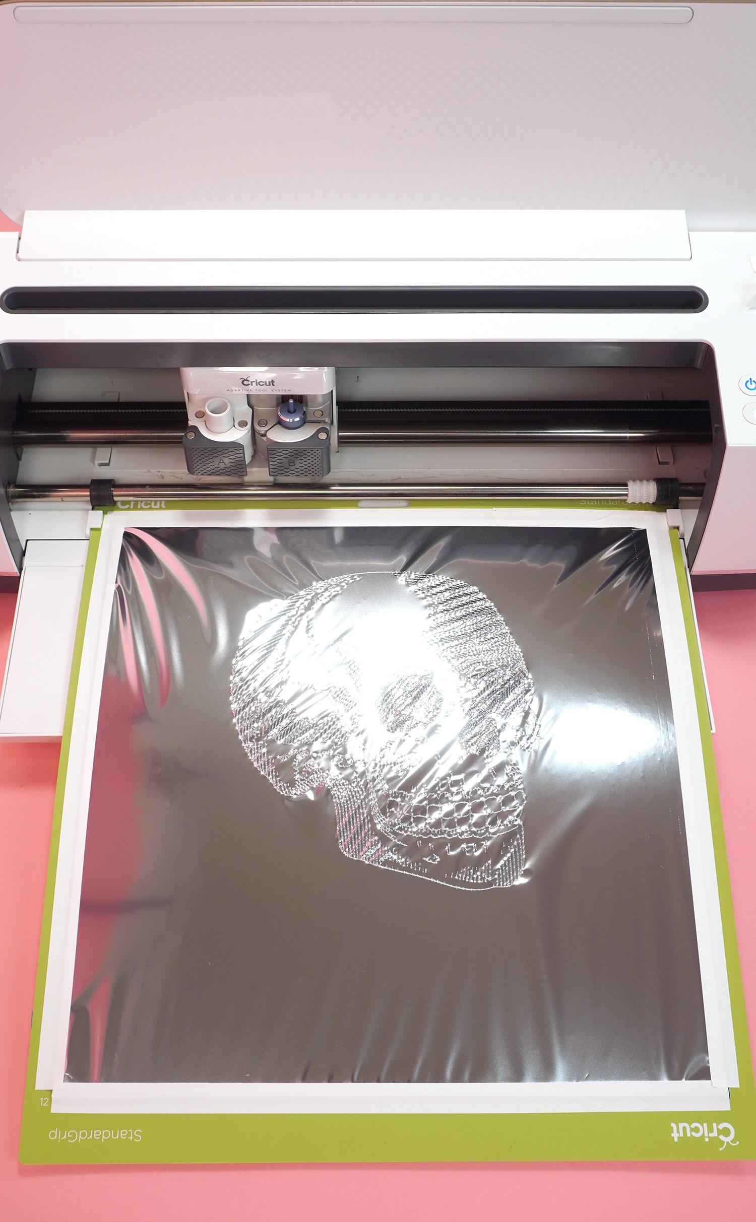 Silver foil with skull design on Cricut mat in Cricut Maker machine