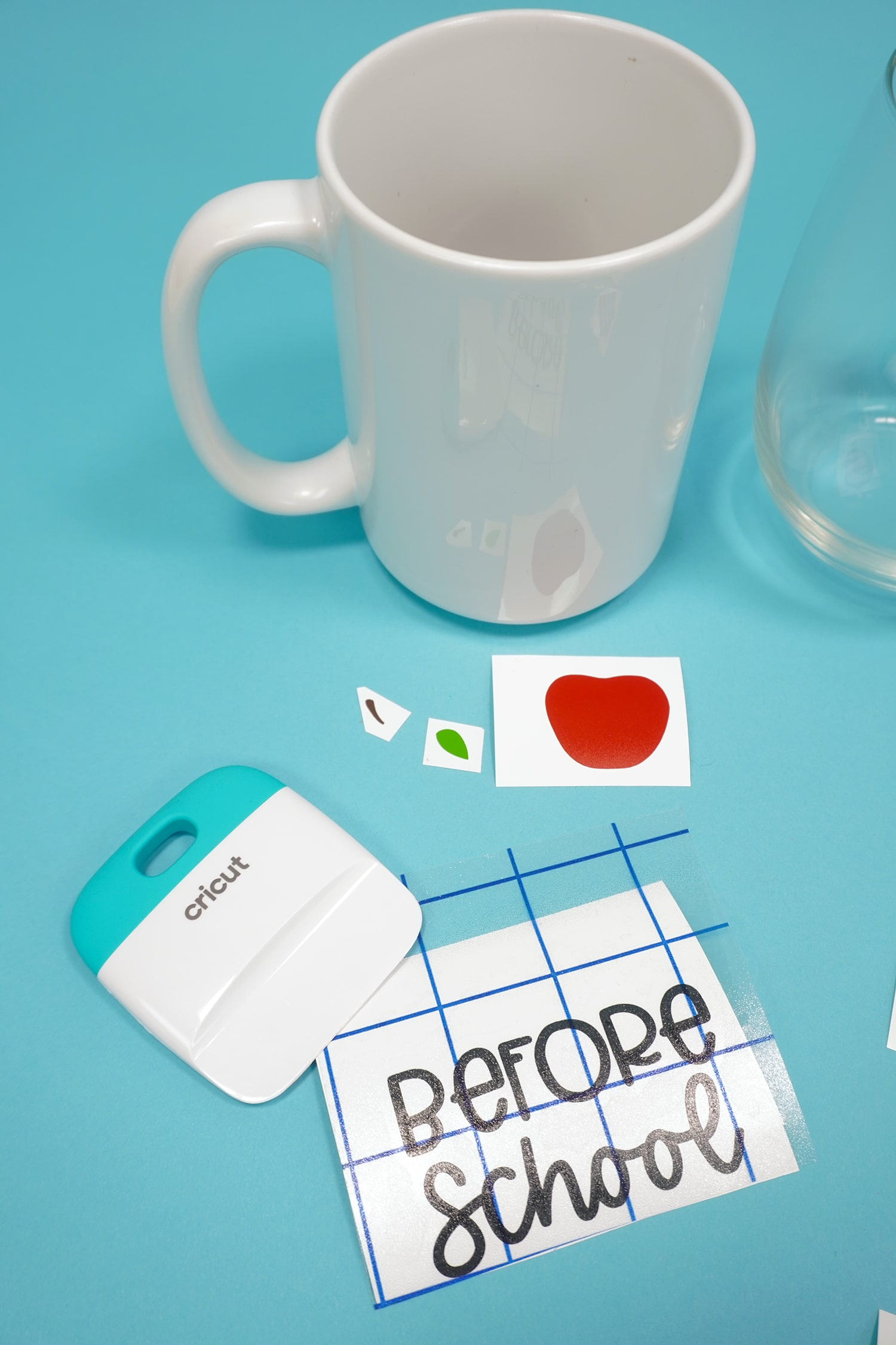 "White mug on a blue background with ""Before School"" and apple vinyl pieces and transfer tape"