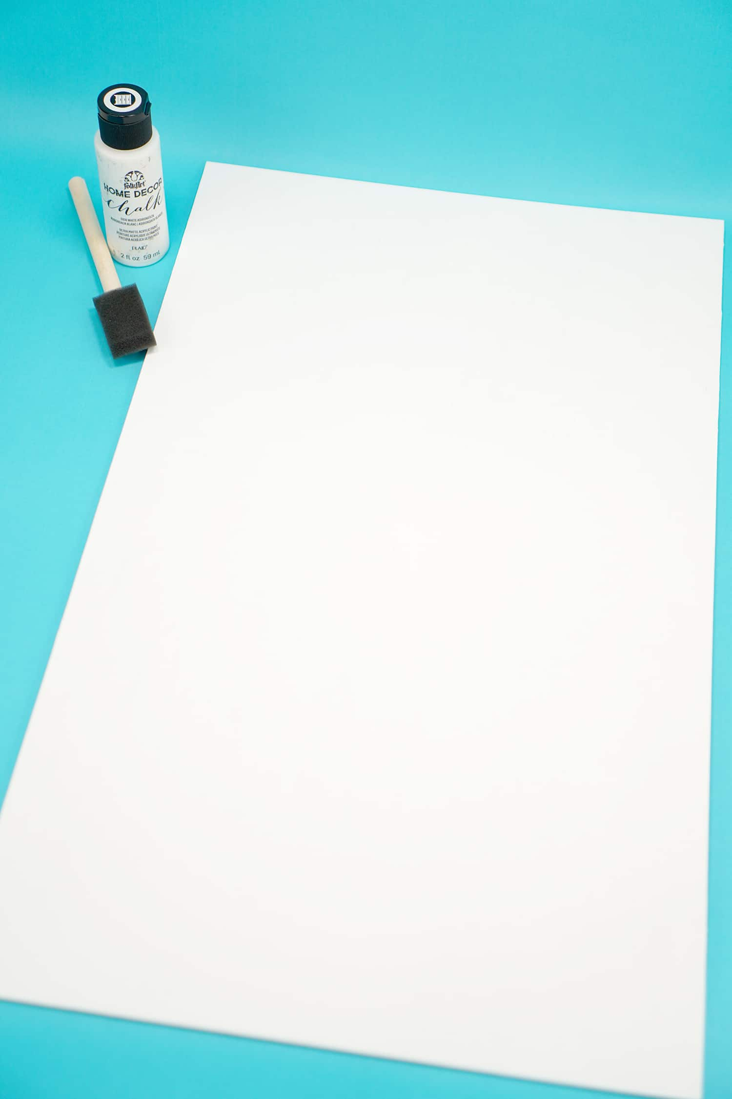 White painted board with white paint and paintbrush on aqua blue background
