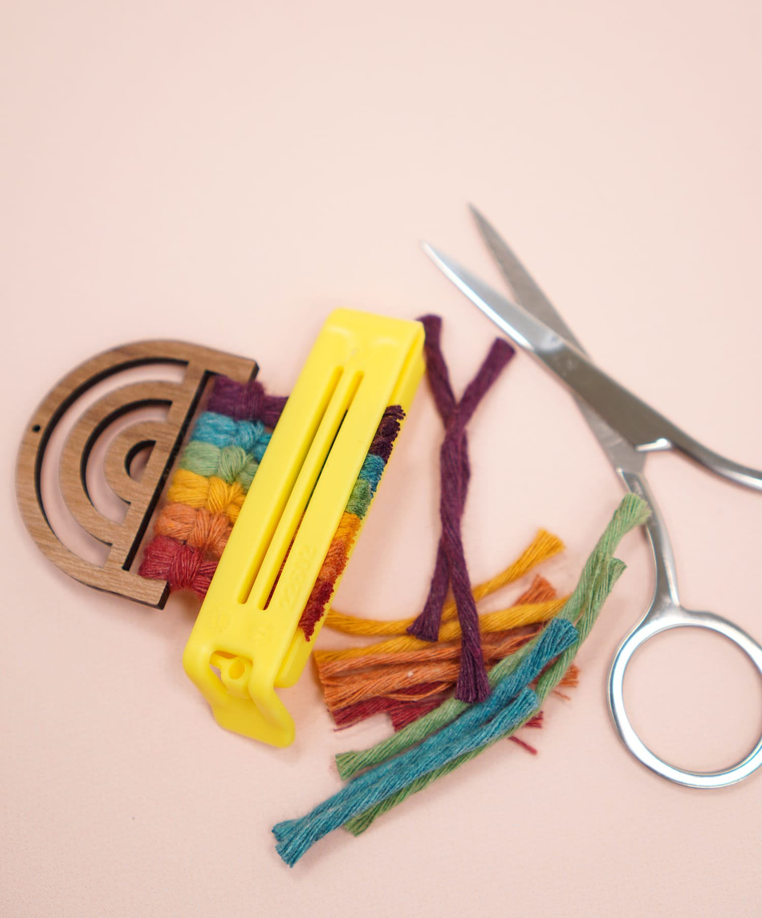Trimmed Rainbow Macrame Earrings on peach background with scissors and bag clip