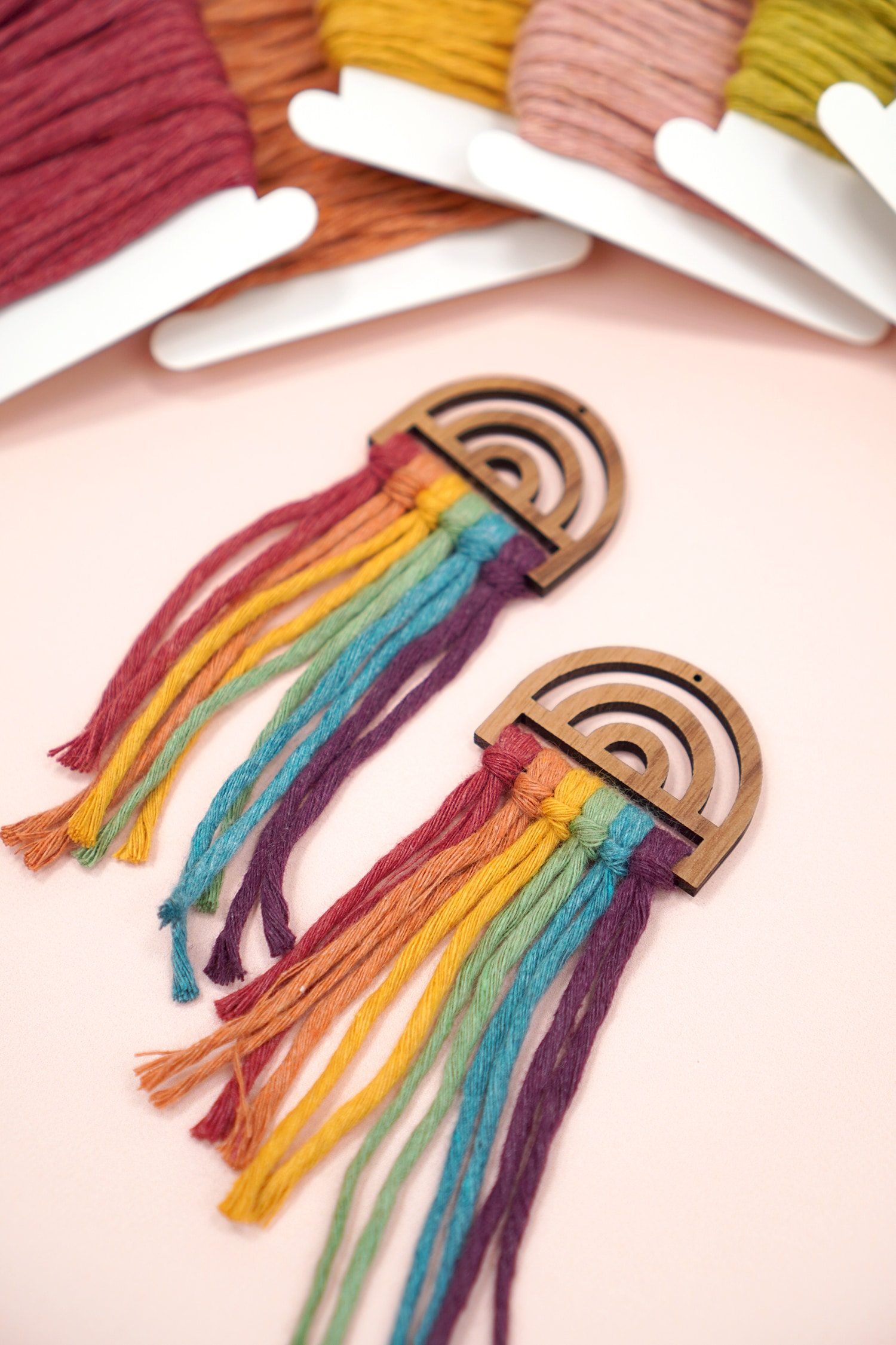 Untrimmed Rainbow Macrame Earrings on peach background with macrame cord