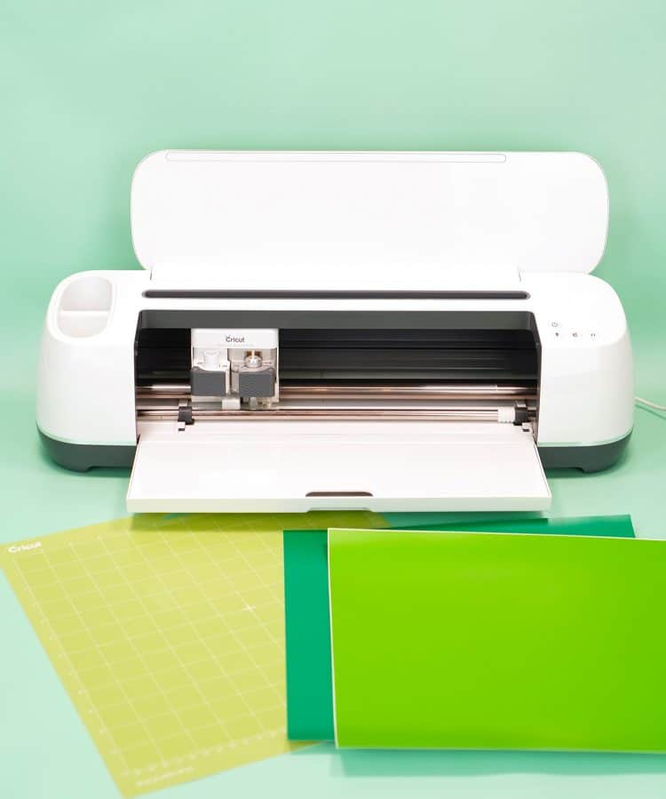 Cricut Maker machine with two shades of green vinyl and mat on mint green background