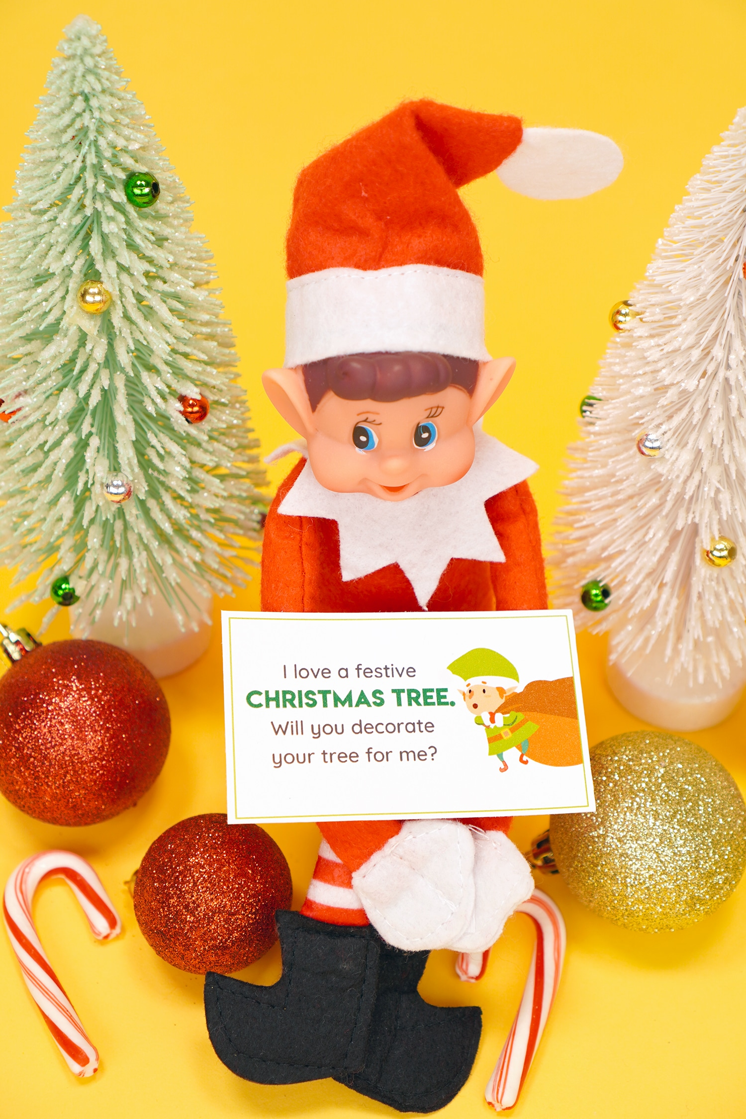 Elf doll holding a printable Elf on the Shelf note card with candy canes, ornaments, and glitter Christmas trees on yellow background