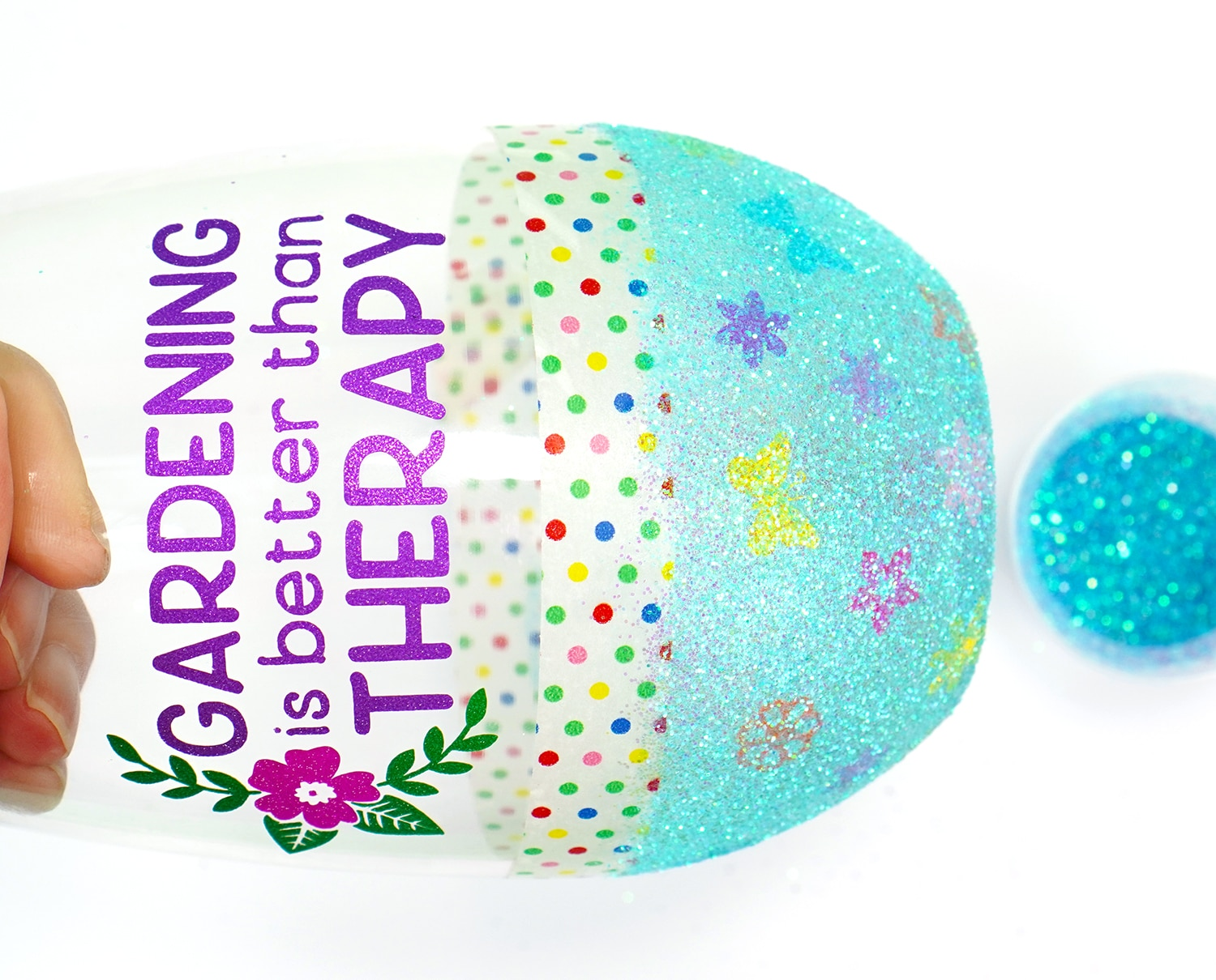 """Applying light blue glitter to the bottom half of a """"gardening is better than therapy"""" wine glass"""