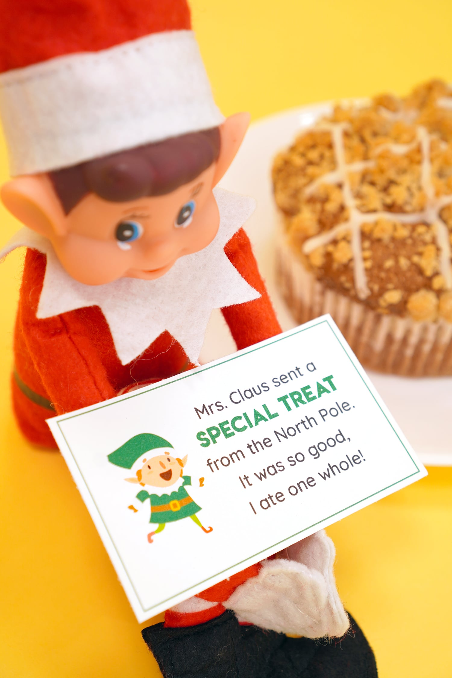 Elf on the Shelf doll with printable Elf on the Shelf note card on yellow background with bakery treats in the far background