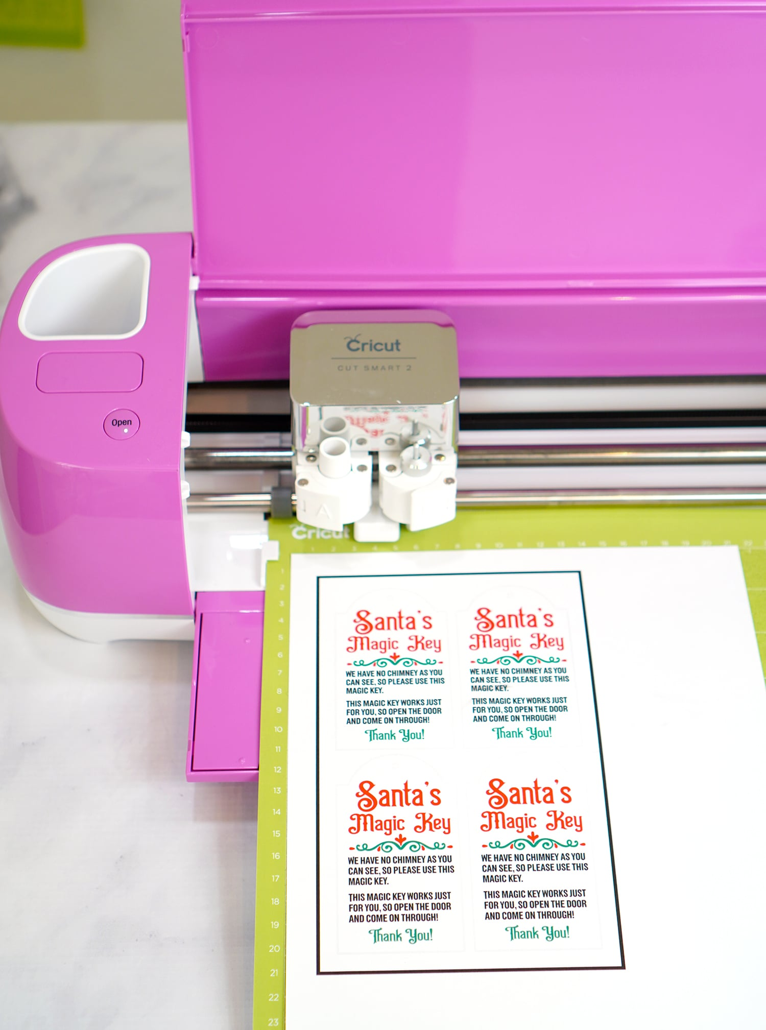 Santa's Magic Key printables on green Cricut mat in fuchsia Cricut Explore machine