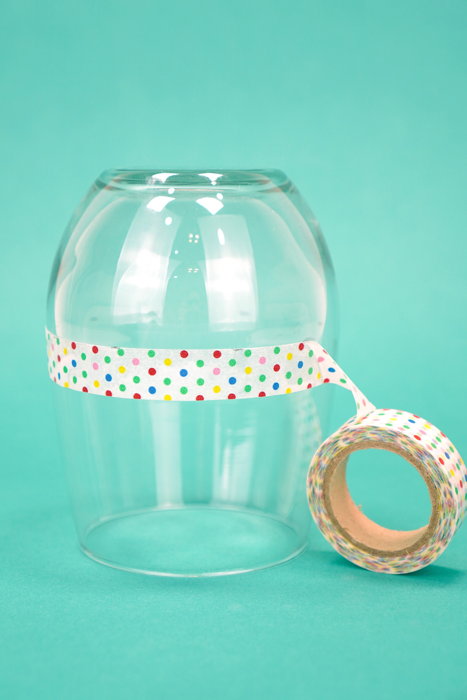 Upside down stemless wine glass on teal background with a ring of polka dot washi tape around glass