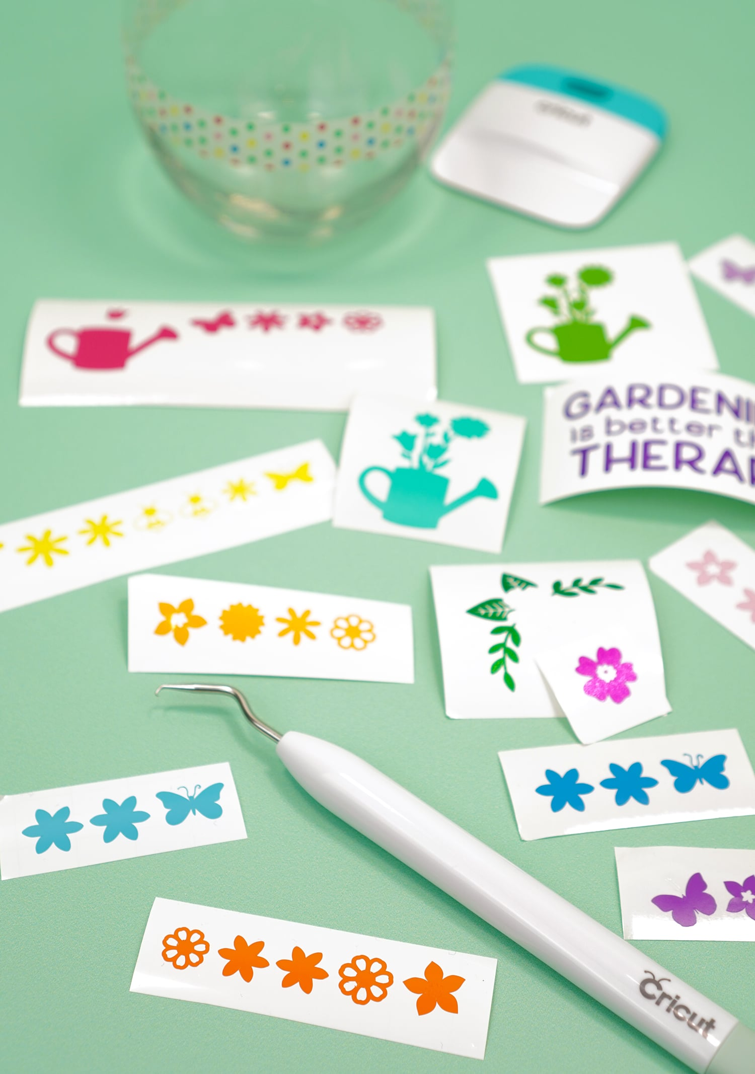 Strips of weeded flower vinyl designs with weeding tool on mint green background