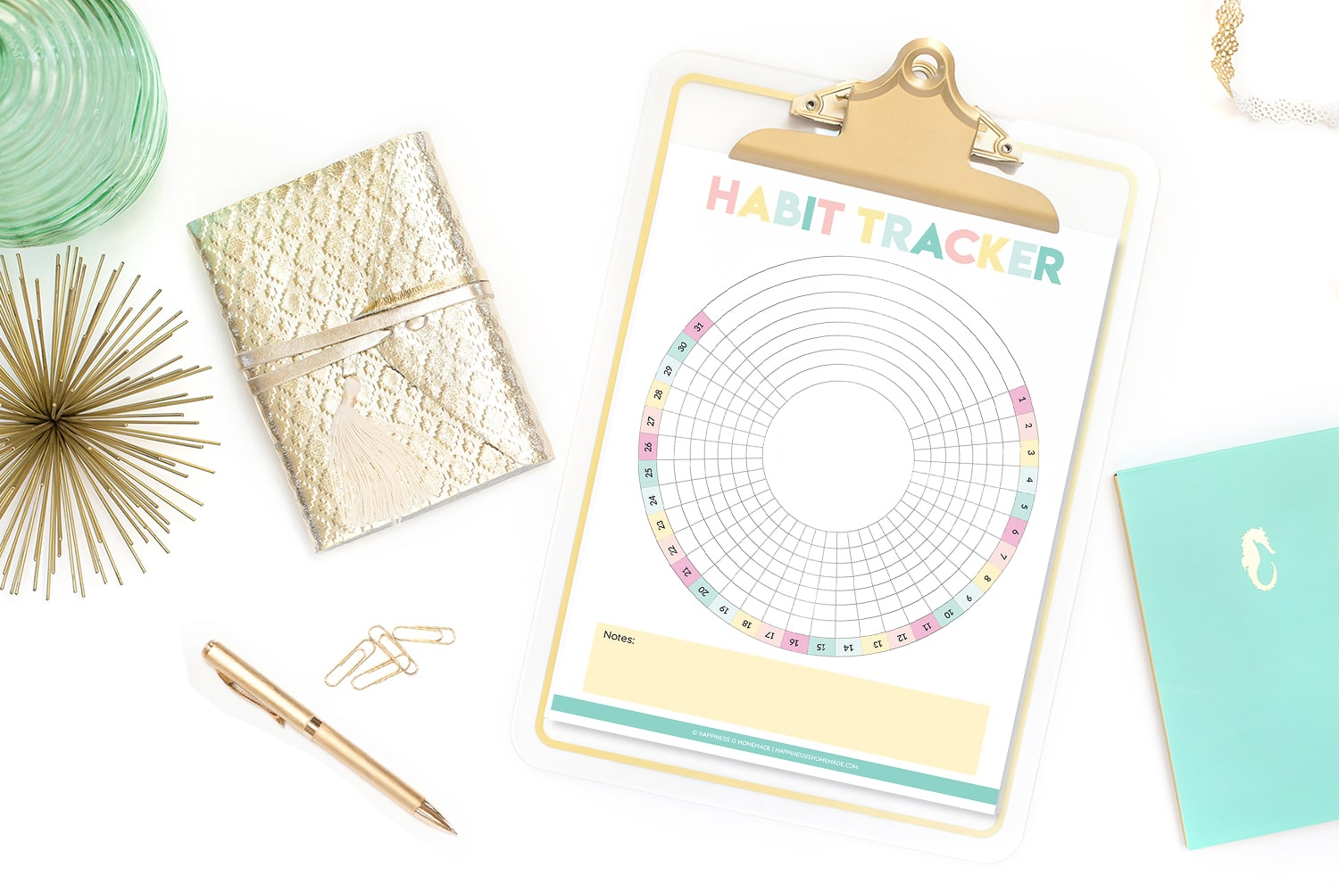 Printable circle habit tracker on gold clipboard on white background with gold wallet, gold pen, and gold paperclips
