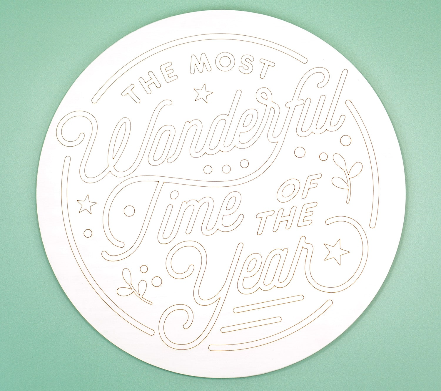 """Round white wood sign with """"The Most Wonderful Time of the Year"""" scored into it with a Glowforge laser"""