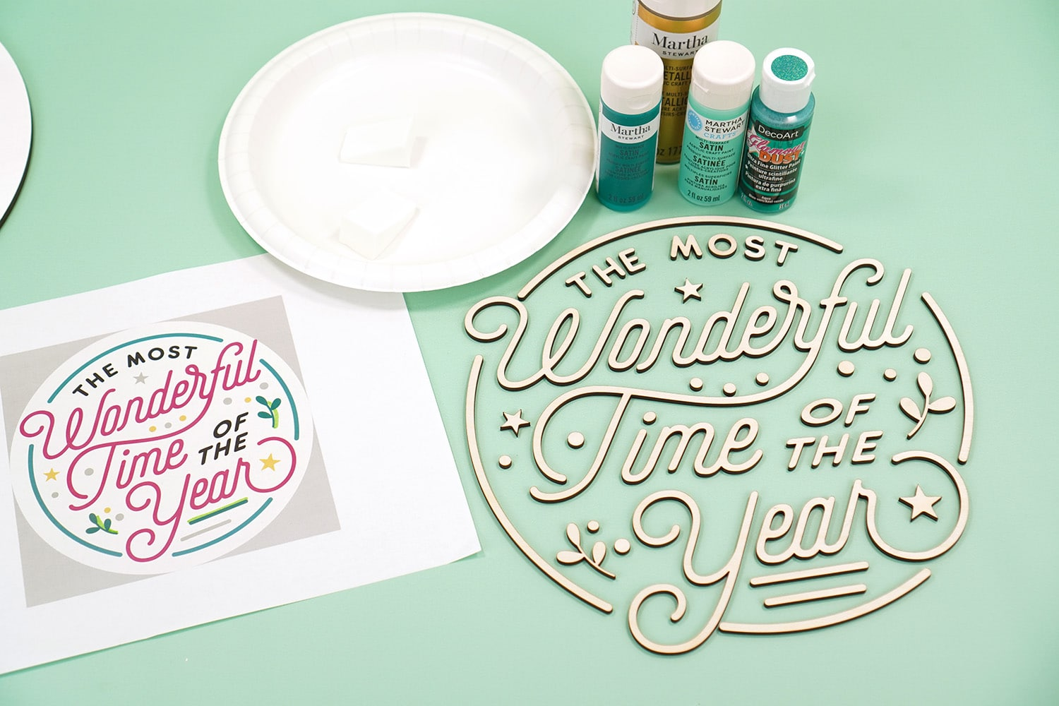 """Mint green background with """"The Most Wonderful Time of the Year"""" Glowforge laser cut wood pieces, paint, and a print out of color palette on white paper"""