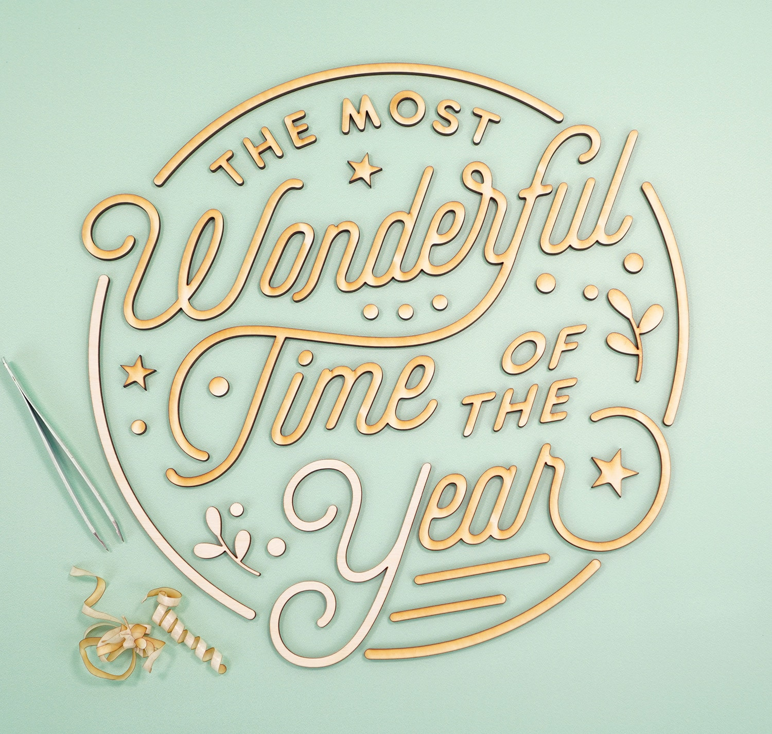 """""""The Most Wonderful Time of the Year' Laser Cut Wood Sign pieces with tweezers and pile of peeled off masking tape on mint green background"""