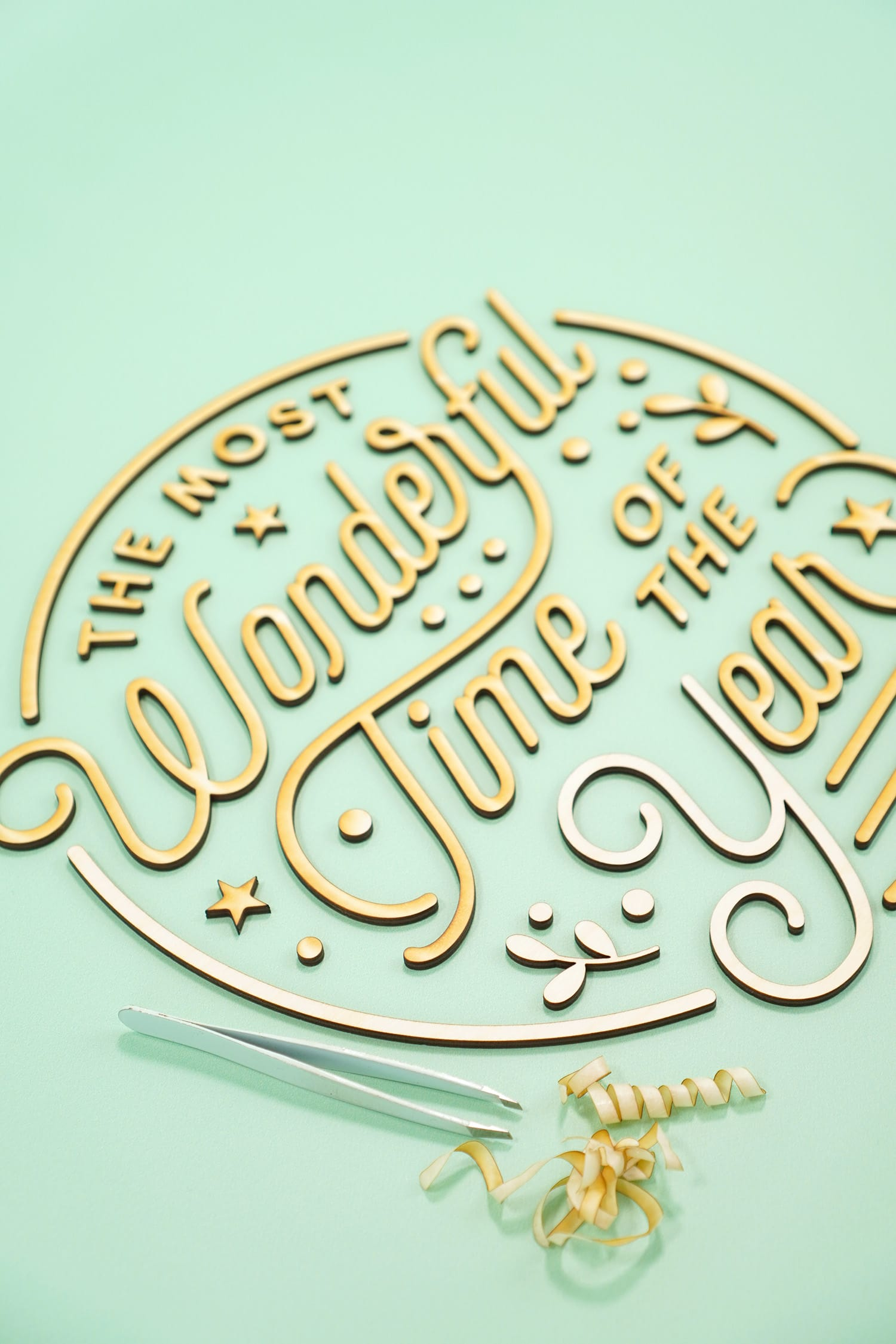 """""""The Most Wonderful Time of the Year' Laser Cut Wood Sign pieces with tweezers and pile of unmasked masking paper tape on mint green background"""