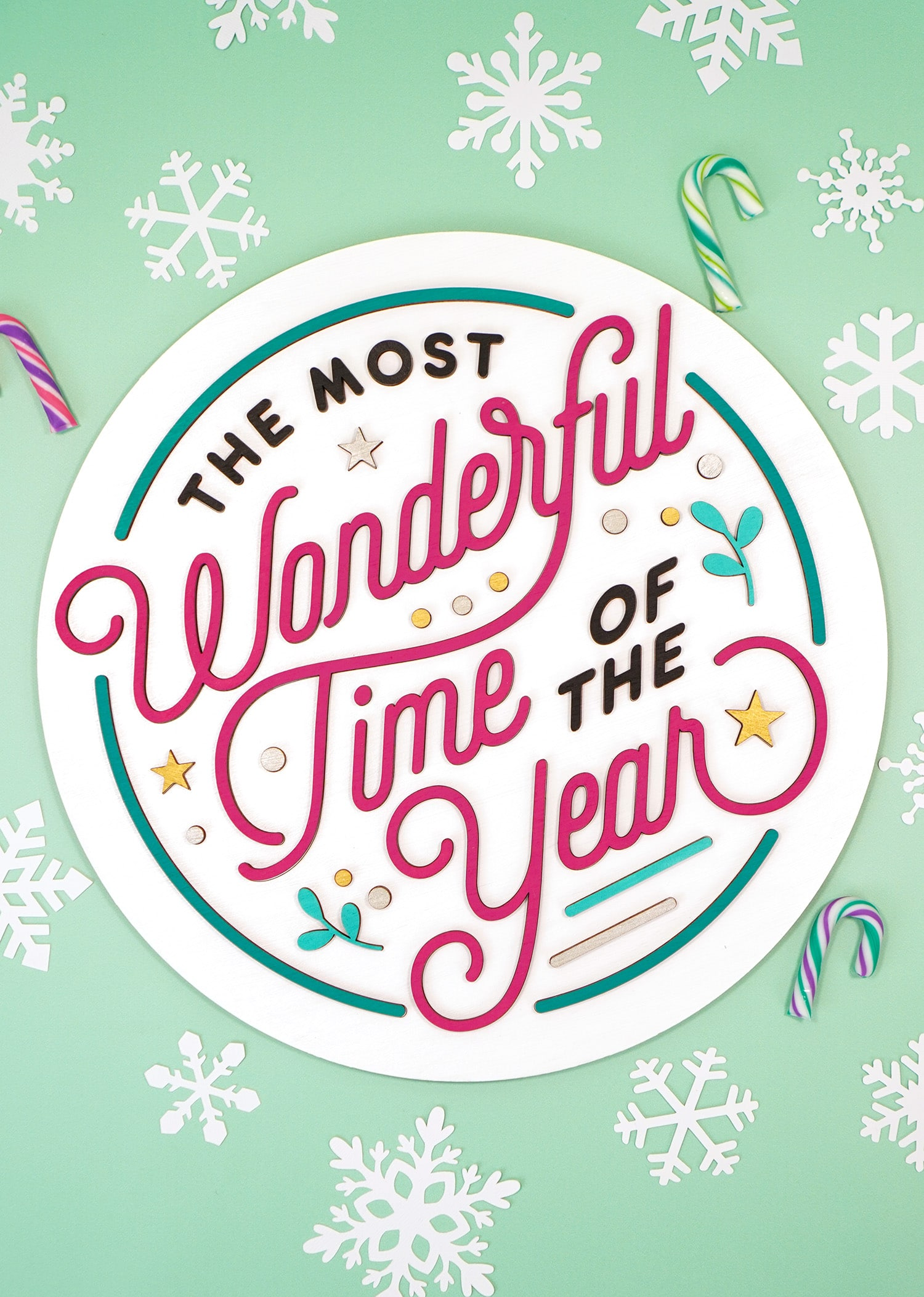 """""""The Most Wonderful Time of the Year"""" Laser Cut Wood Sign on mint green background with white paper snowflakes and colorful mini candy canes"""