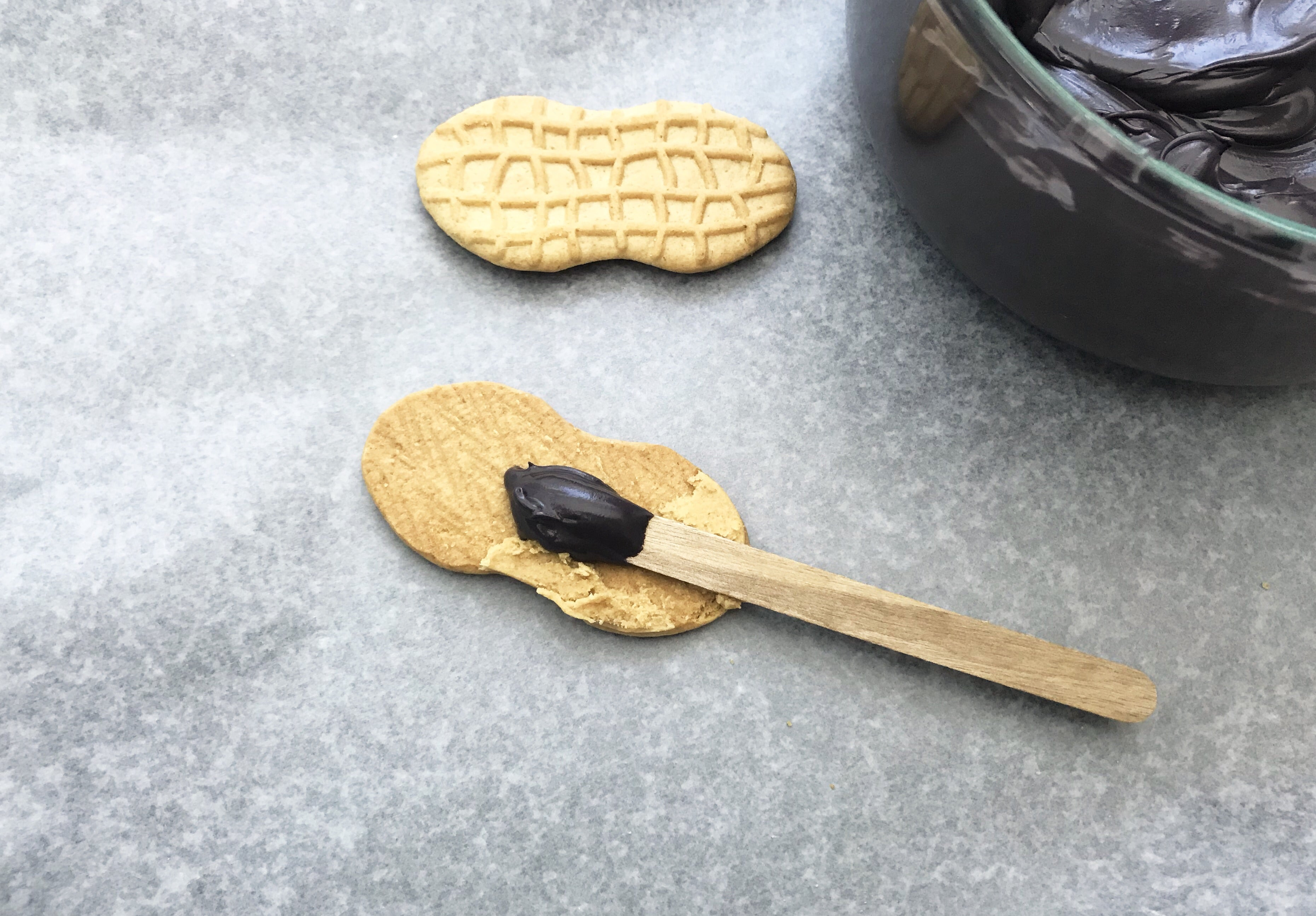 Icing on a popsicle stick being placed on a nutter butter cookie on a grey background