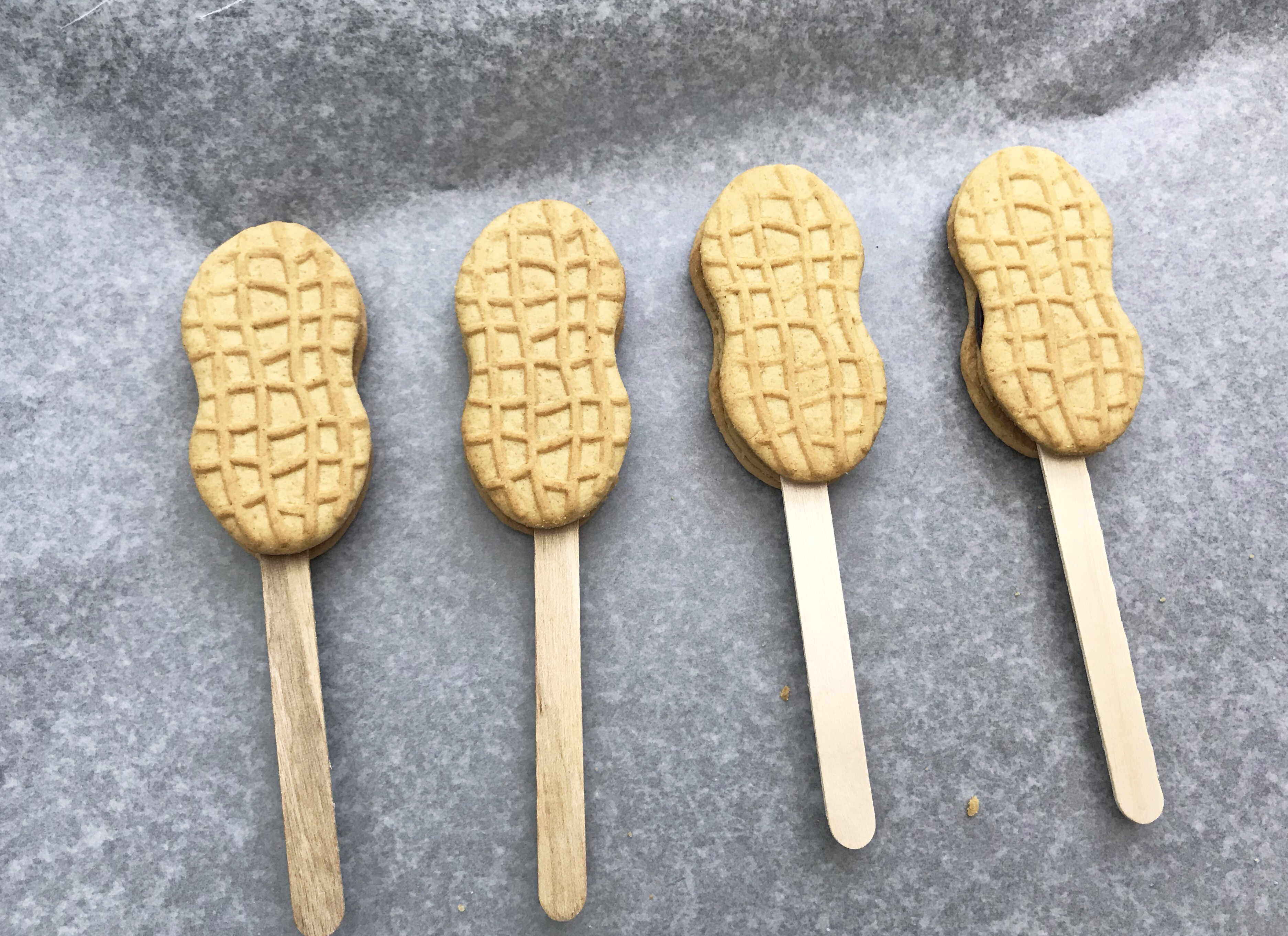 4 nutter butter coookies with popsicle sticks on a grey background