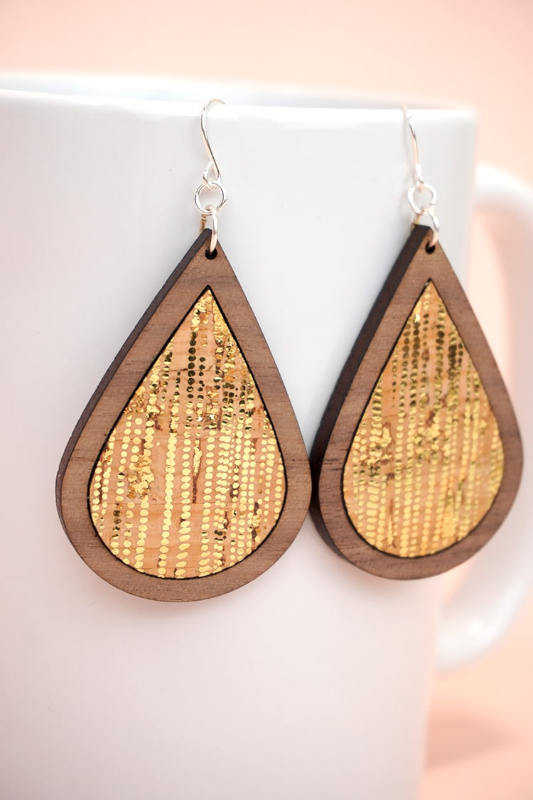 Close up of gold dotted cork and laser cut wood earrings