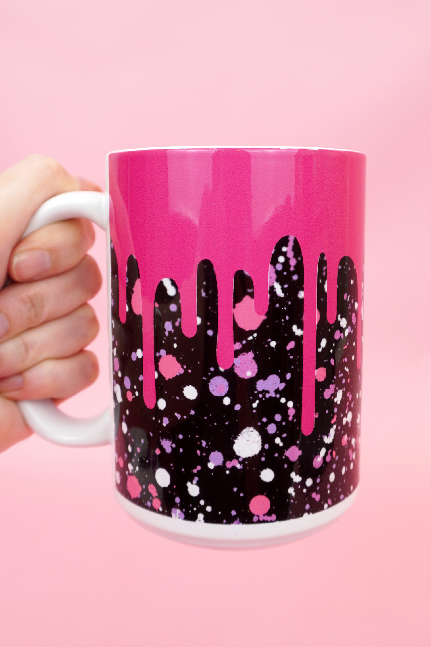 """Hand holding pink and black """"drippy"""" mug on a pink background"""