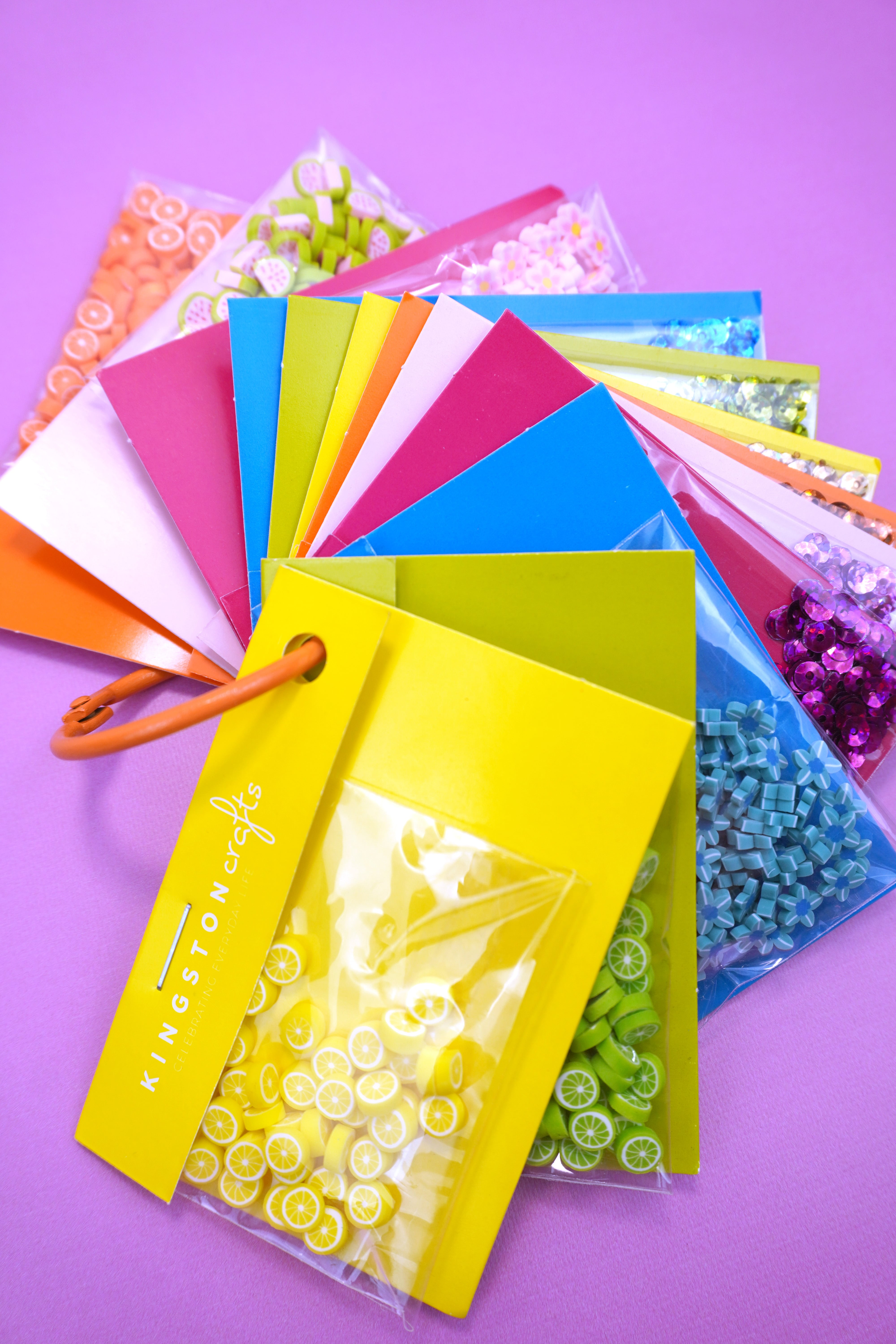 Kingston Crafts shaker embellishment set in colorful packages on purple background