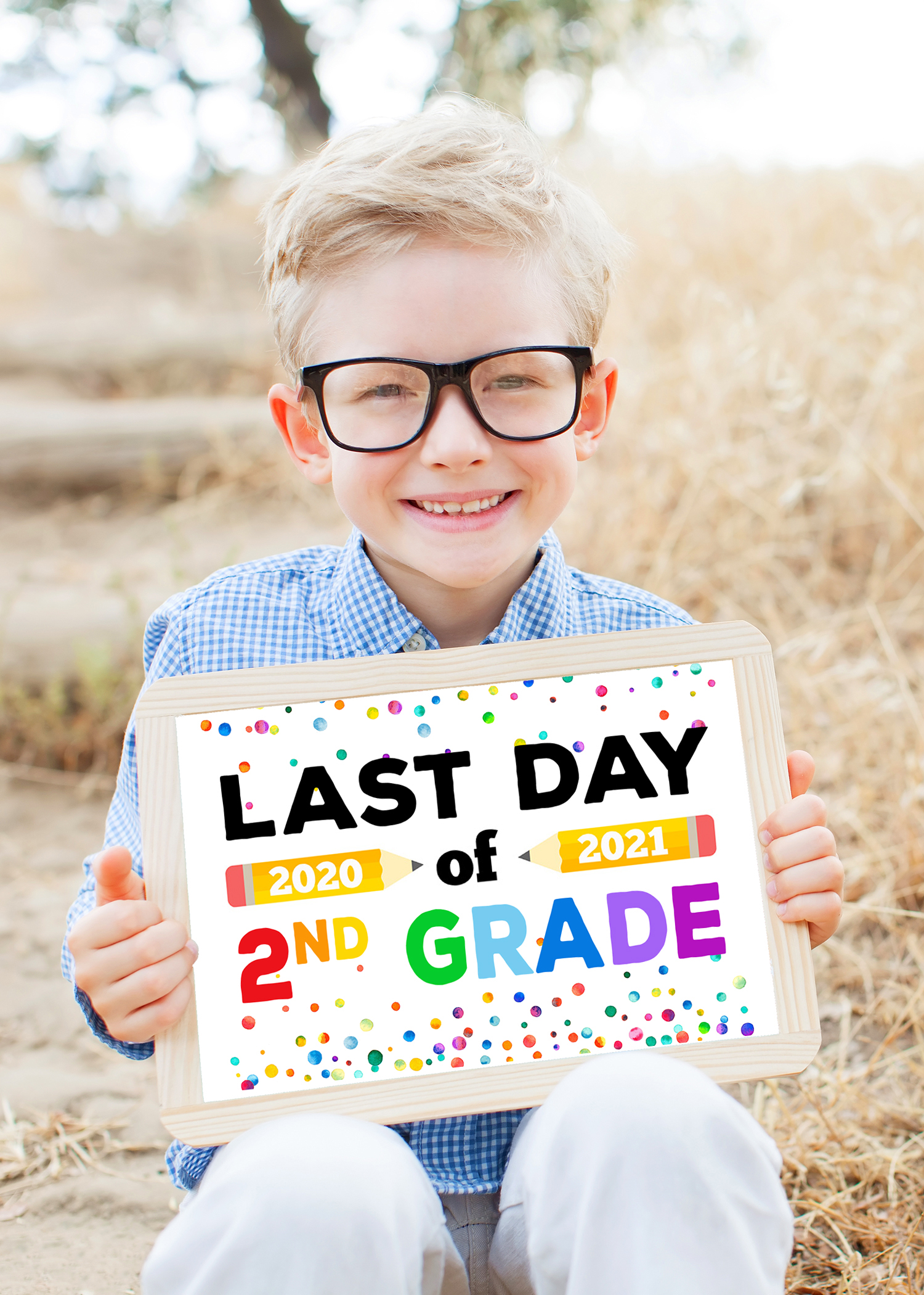 Blonde boy with glasses holding a Last Day of School sign