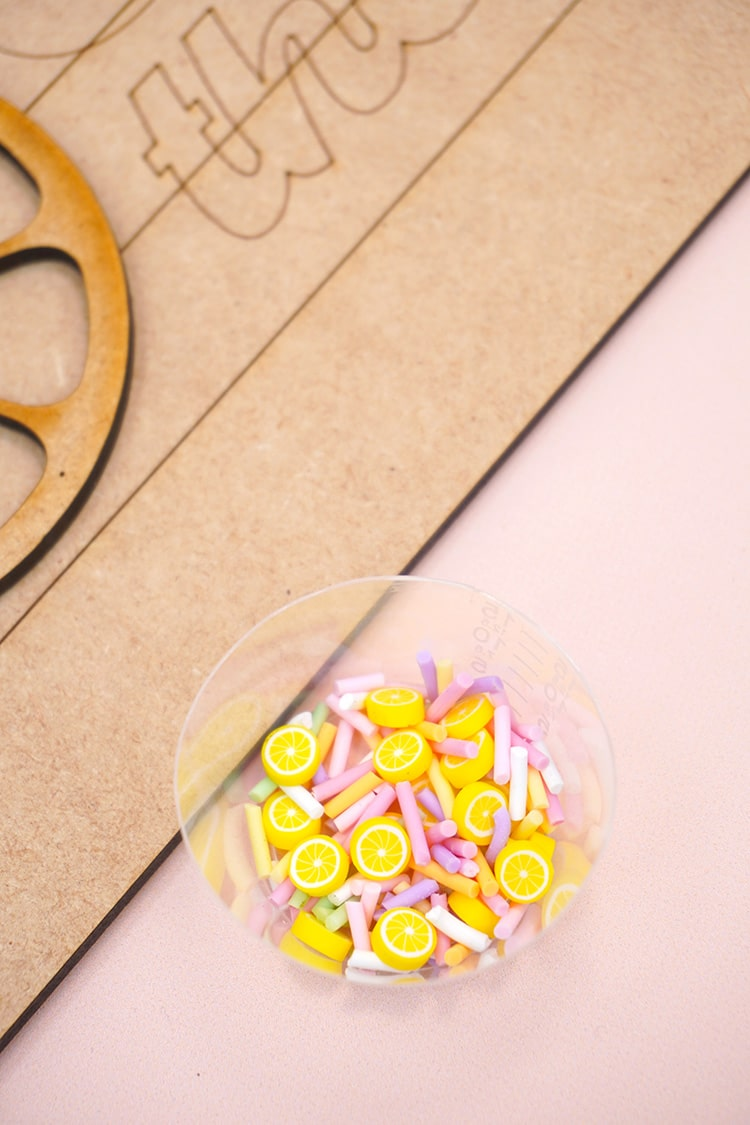 Small clear cup of polymer clay lemon slices and sprinkles on peach background