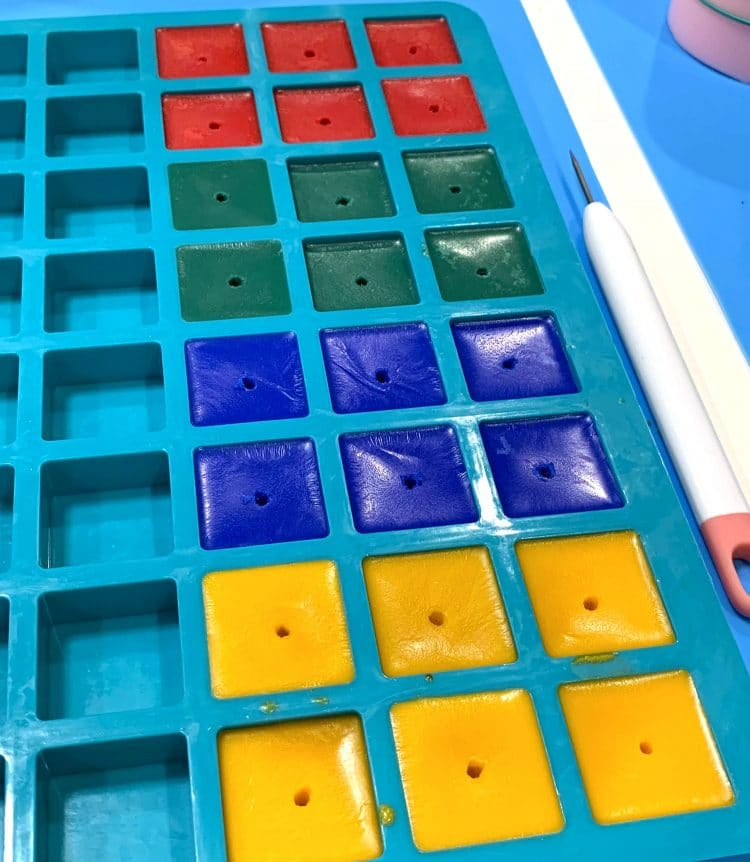 Red, green, blue, and yellow wax cubes with small center holes in silicone mold