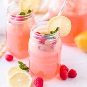 Pink raspberry flavored lemonade in mason jar glasses with striped straws, lemon slices, and fresh raspberries