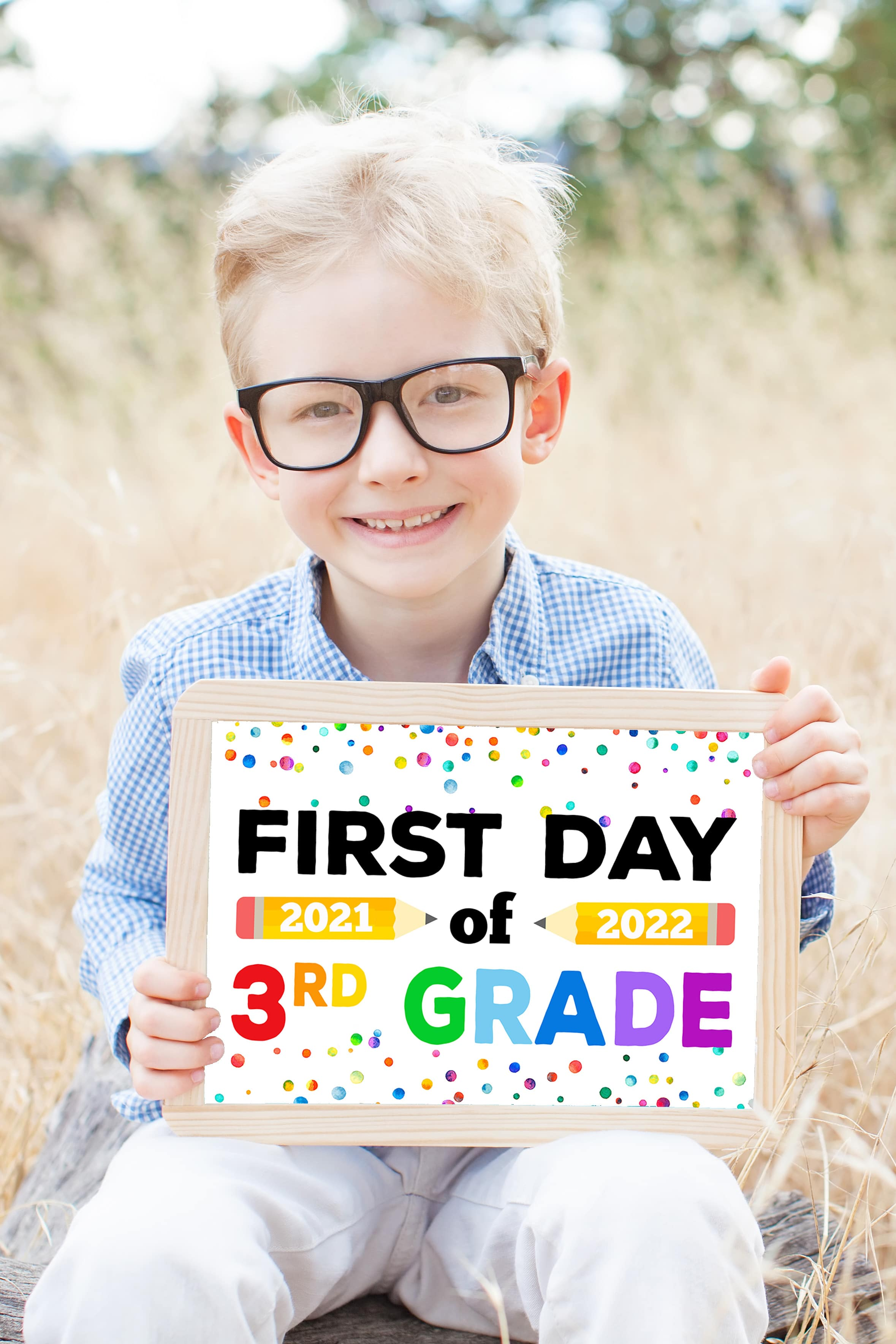 """Cute blonde boy with glasses holding a """"First Day of School 2021-2022"""" sign printable"""