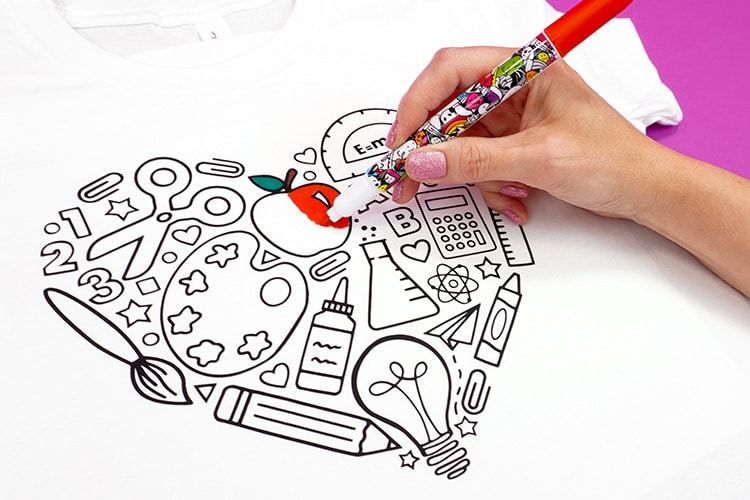 Close up of hand with red fabric marker coloring a back to school shirt