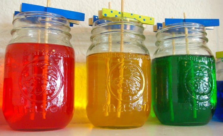 three mason jars full of colorful sugar solution and wooden skewers
