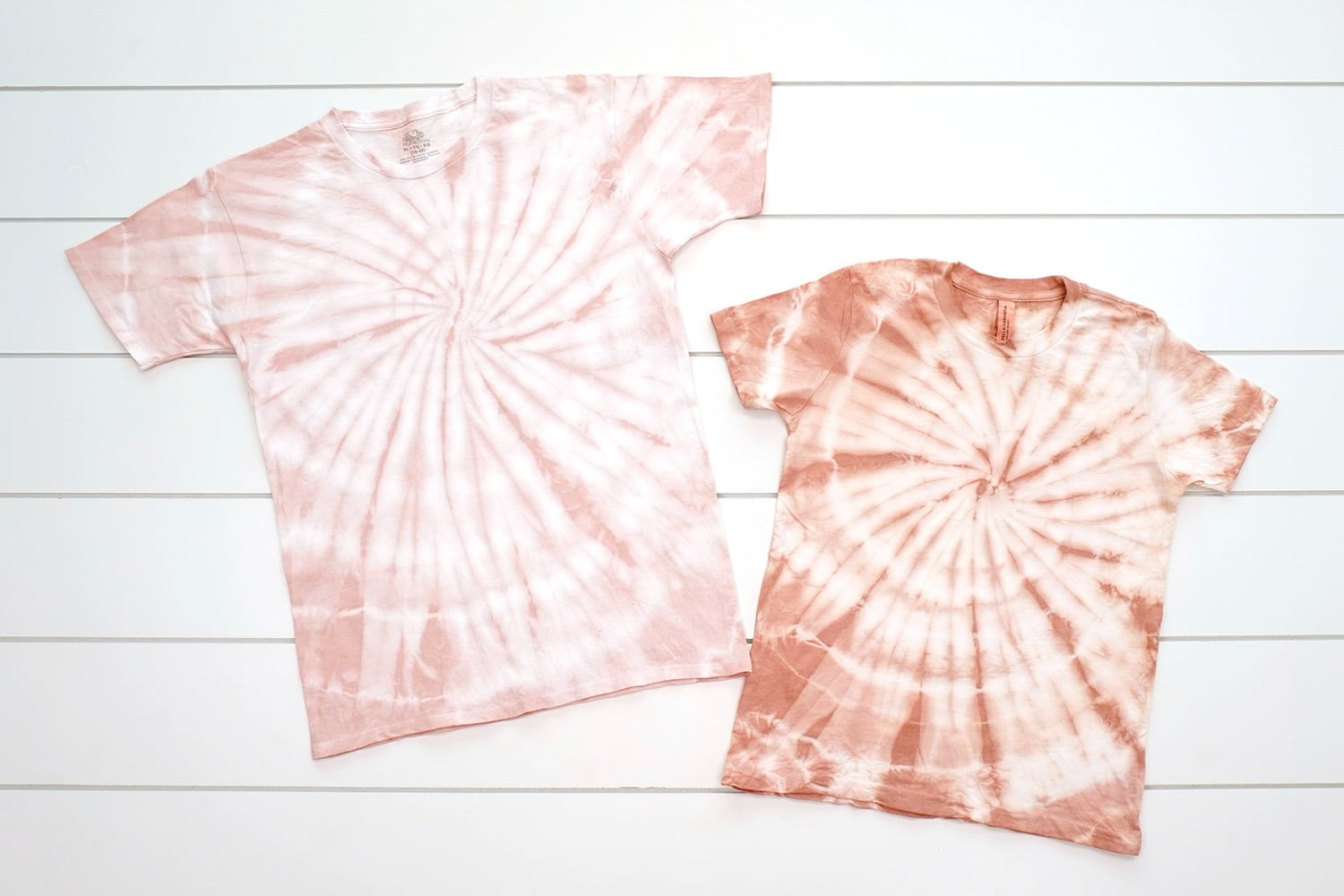 two spiral tie-dye shirts on a white background, one blush pink color and one a peachy pink