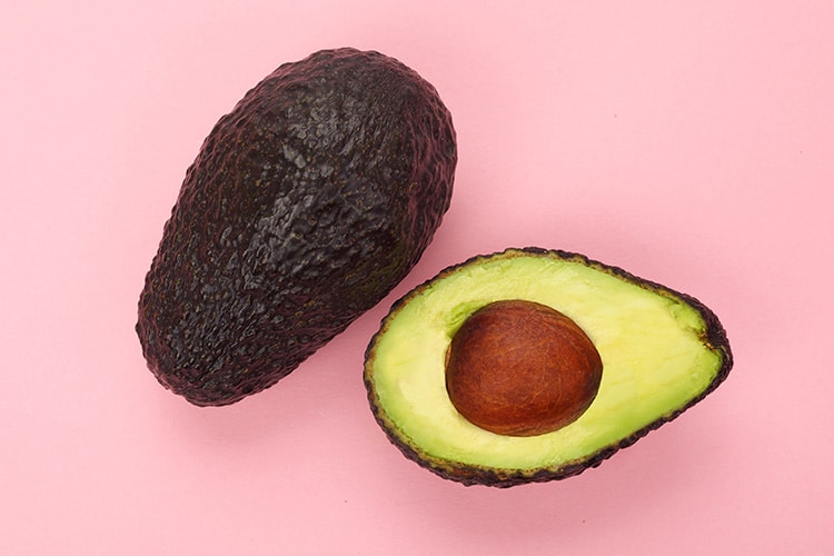 Whole and halved avocados on pink background