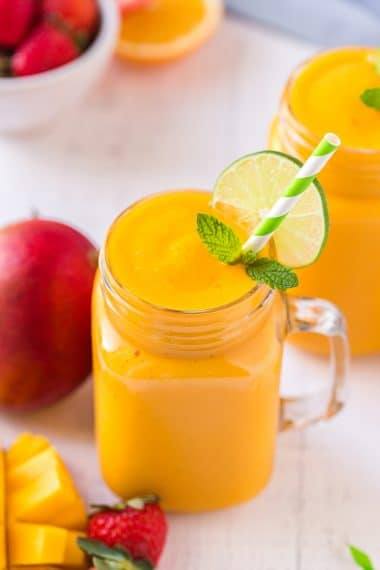 Mango smoothie in a mason jar glass with a lime wheel and a green striped straw