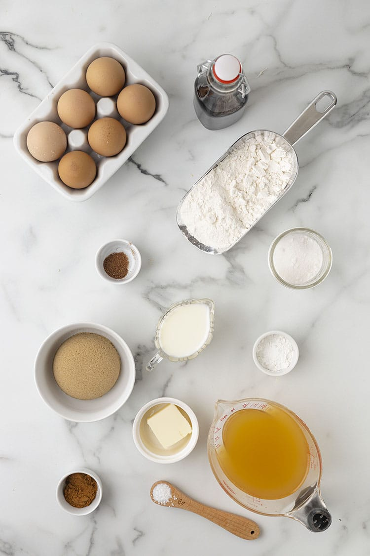 Apple cider donut ingredients on a grey and white marble background