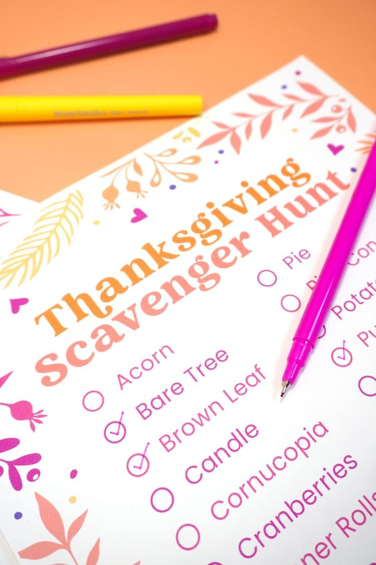 "Close up of words ""Acorn, Bare Tree, Brown Leaf, Candle"" etc. on a printable Thanksgiving Scavenger Hunt game on orange background"
