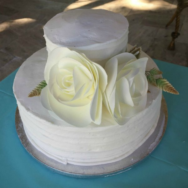 How to Order a Cake from Sam s Club two tier white wedding shower cake from Sam s club with white flowers on a  blue tablecloth