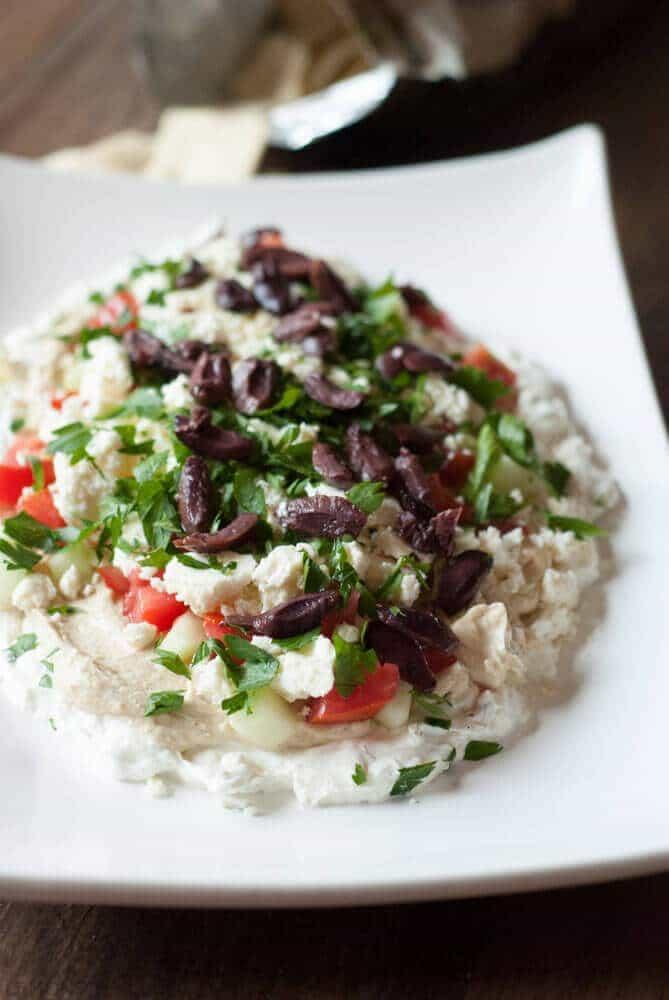 Mediterranean 7 layer dip that is loaded with cream cheese, Greek yogurt, hummus and veggies! Absolutely delilous! www.lemonsforlulu.com