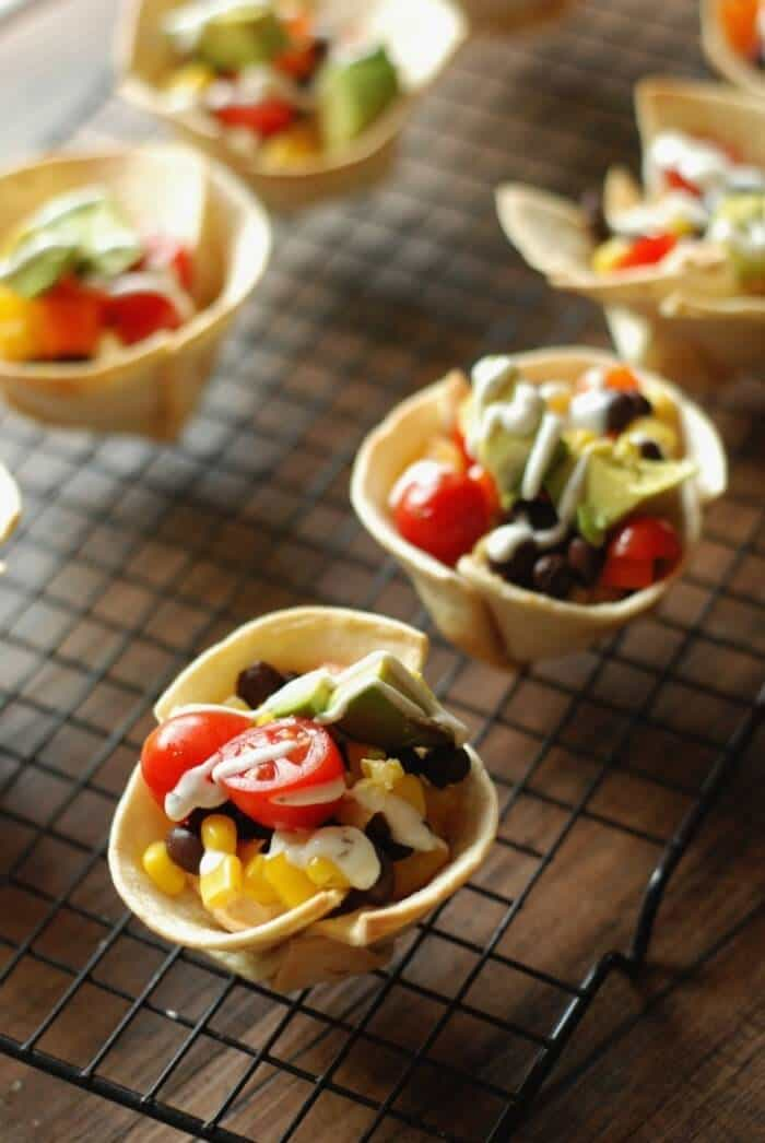 Five veggie taco cups with beans, tomatoes, corn and sour cream on a black cooling rack.