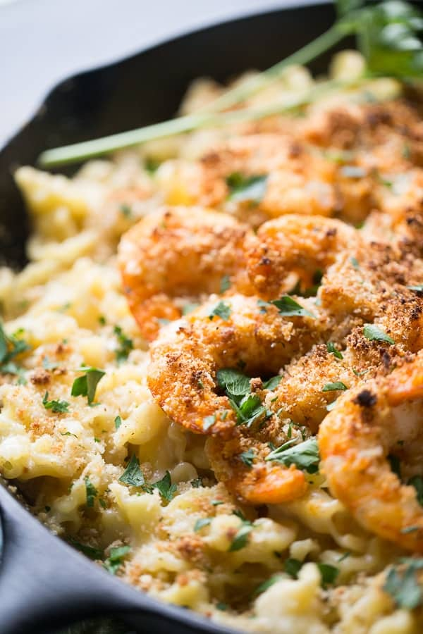 Close up of juicy Cajun Shrimp on top of Mac and Cheese in a large cast iron skillet.