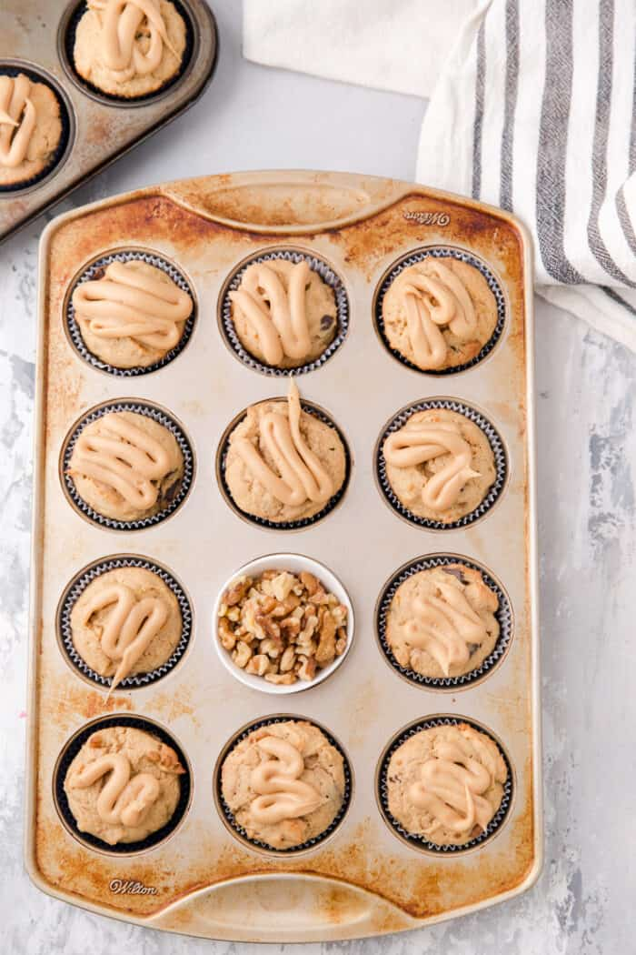 tin of banana muffins with nuts in the center cup