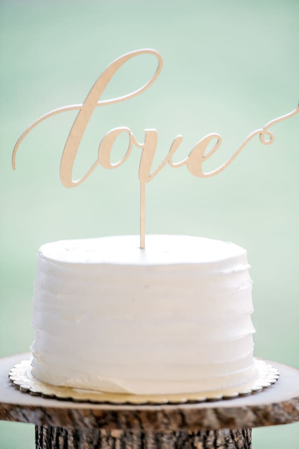 Why a Simple Wedding Cake Design Is the Way to Go buttercream ruffle cake with love cursive topper