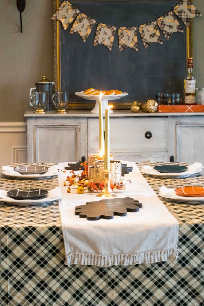 wooden leaves and gold gilded centerpieces grace this thanksgiving table
