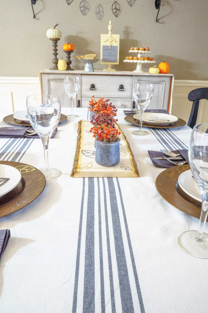 Looking for a modern rustic Thanksgiving tablescape? Use your Cricut to make these DIY chargers, a raw wood centerpiece, and wall art for the holiday!